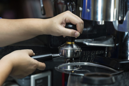 tamper: Man is using a tamper to press freshly ground morning coffee into a coffee tablet Stock Photo