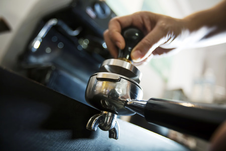 coffee grounds: Barista compresses coffee grounds with tamper