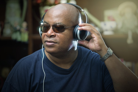 Attractive man listening to music on a set of stereo headphones