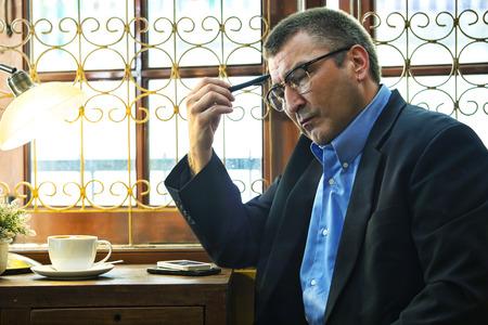worried businessman: Worried businessman sitting in cafe Stock Photo