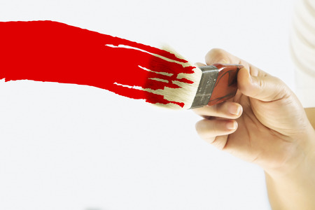vibrant paintbrush: Hand painting the white wall with red paint Stock Photo