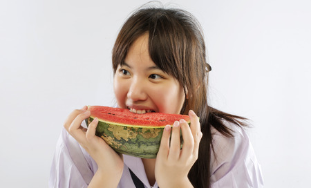 enjoing: Asian girl enjoing a water-melon isolated on white background