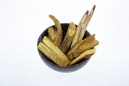 oleoresin: Dry Turmeric roots or barks in wooden bowl isolated on white background