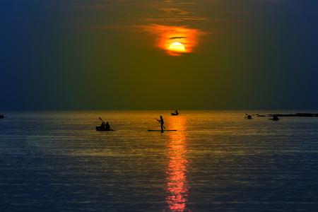 ocean kayak: Tourists kayaking on tropical island at sunset Foto de archivo