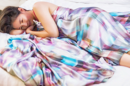 topless model: Beautiful young lady covered by Brightly colored blankets laying on bed Stock Photo