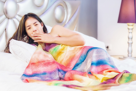 wellness sleepy: young woman is yawning as she lays in her bed.