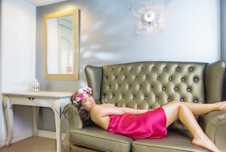 pyjama: Beautiful young woman  in red silk pyjamas laying on the sofa Stock Photo