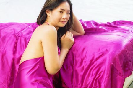 pyjamas: The girl woke up sitting by bed in red silk pyjamas