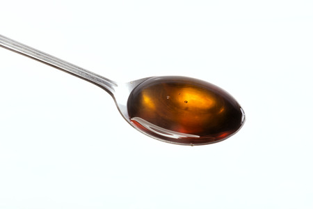Honey on a spoon stainless steel over white background