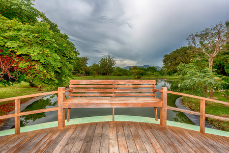 wooden seat on the bridge across the pond in the park Stock Photo