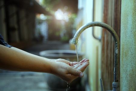 시골의 수도꼭지에서 손을 씻기, 물의 흐름을 줄입니다. 스톡 콘텐츠