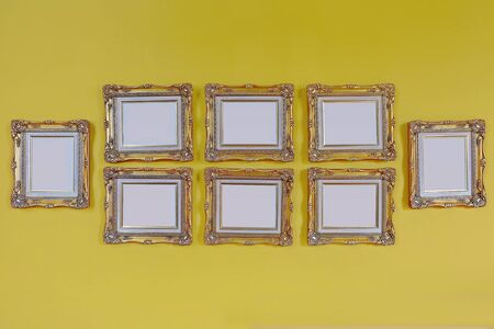 Antique golden frames on the wall. Art gallery. Objects group on yellow background Stockfoto