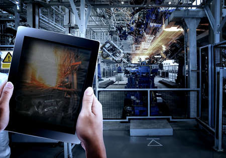 Engineer hand using tablet with machine real time monitoring system software in smart factory automotive industry