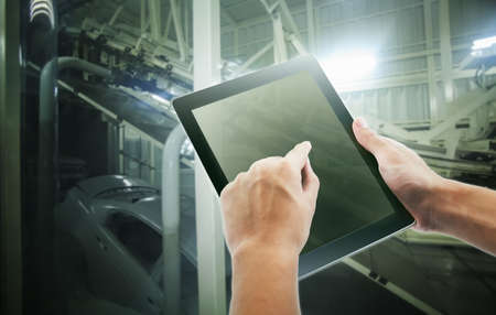 Engineer hand using tablet with machine real time monitoring system software in smart factory automotive industrial Industry ,Coating process