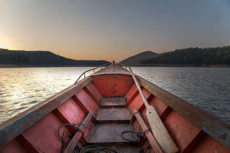 Prow boat on lake at sunset