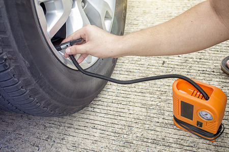 A man checking air pressure and filling air in the tires of car