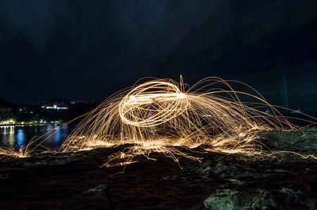 light ball swing fire on beach night party Stockfoto