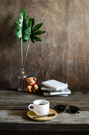Wood desk with books and sunglasses still life work space and hot coffee