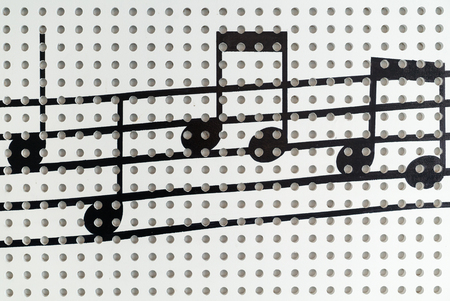 musical score: Music note on the white wall background