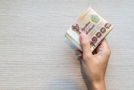money packs: Hand giving stack of thousand bath Thai money with copy space