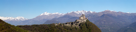 Panorama of the Sacra di San Michele (Saint Michael Abbey) , the symbol of the Italian region of Piedmont,  In the background the mountains of the Val di Susa. Stock Photo