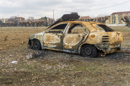 A burnt car wreck in the field and town houses as background. Reklamní fotografie