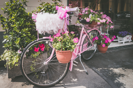 Vintage pink bicycle standing on the street - with many flowers.
