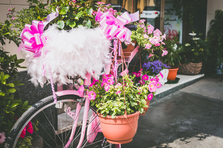 Particular of a vintage pink bicycle standing on the street - with many flowers. 版權商用圖片