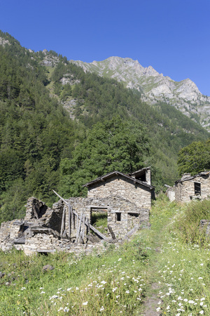 path passing through an abandoned village in alps mountains full of different houses and destroyed buildings. Piedmont. Italy