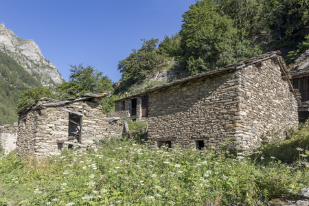 old and  abandoned village in alps mountains full of different houses and destroyed buildings. Piedmont. Italy Stock Photo