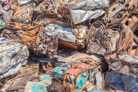 crushed cans: Crushed aluminium cans and other scrap metal is reduced to square blocks when recycled at a scrap yard.