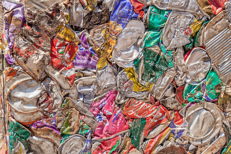 crushed cans: Crushed aluminium cans are reduced to square blocks when recycled at a scrap yard.