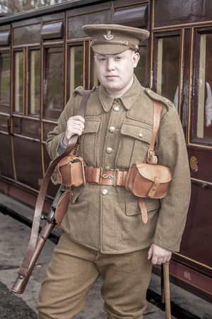 ww1: Tanfield, UK, March 13, 201: Reenactor WW1 weekend. A young british soldier about to board a steam train at Andrews House station, Tanfield Railway, the oldest railway in the world.