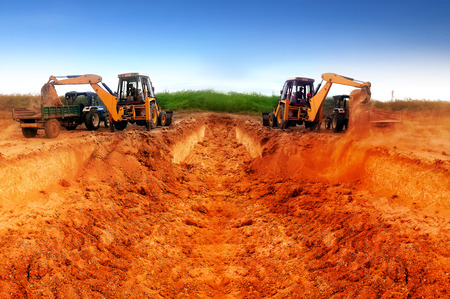 camera shot on earth mover working in a site tractor being loaded red sand