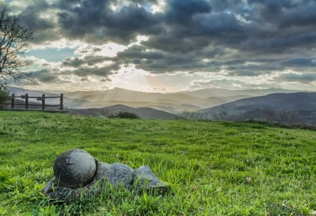 The sun s rays filter through the dark clouds in the morning panorama of the Tuscan hills  photo
