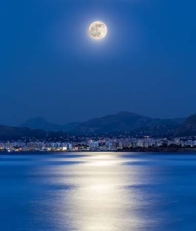 The moonlight is reflected on the sea in the bay of the city of Palermo (Italy). Stock Photo