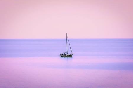 imminent: A boat with its sailors surrounded by an calm sea and the colors of the imminent sunset