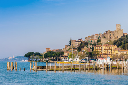 An small and beautiful medieval village, with its small port, on the shore of Lake Trasimeno in Umbria (Italy) Stock Photo