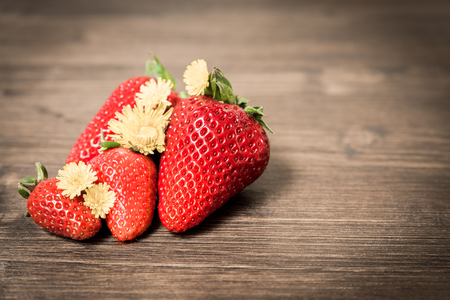 Strawberries, typical summer fruit. A composition with few fruits placed on an old table. A good and healthy type of fruit that contains few sugars. Stok Fotoğraf