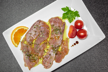 A delicious fresh Mediterranean tuna carpaccio dressed with extra virgin olive oil, chives, parsley and a few drops of orange juice. Decorated with Pachino tomatoes, parsley, a slice of orange and a few drops of Modena balsamic vinegar cream