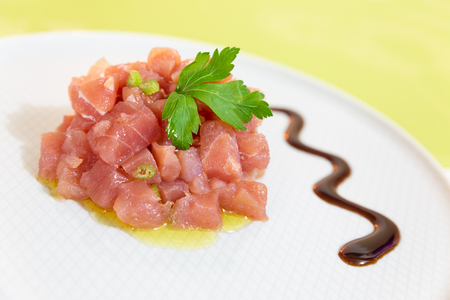 A delicious tartare of fresh Mediterranean tuna. Seasoned with extra virgin olive oil and parsley The dish is decorated with parsley and balsamic vinegar of Modena