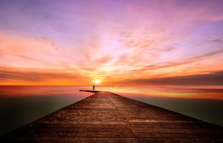 A person on a pier observes and contemplates a splendid sunset