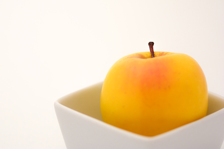 dietetics: Golden apple in a white square container on a white background