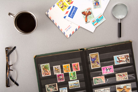 High angle view of a stamps collection with eyeglasses, a cup of coffee, a magnifyer and letters