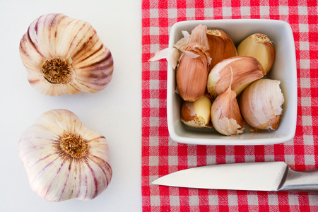 High angle view of garlic and shallot cloves on a rustic towel and white background