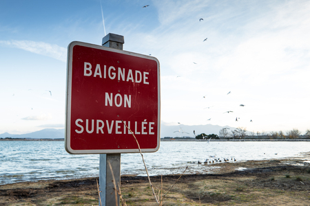 Closeup of a French warning sign of a non supervised swimming lake Stock Photo