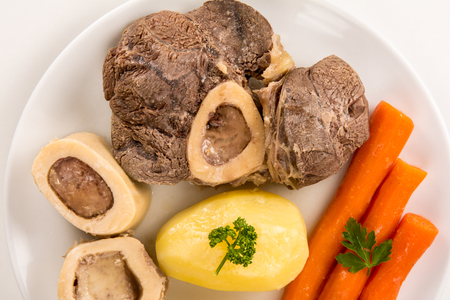 High angle view of a closeup of a pot au feu, a french beef stew on a white plate and background