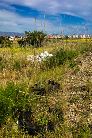 Discarded old tyres and plastic bags grassy wasteland Stock Photo