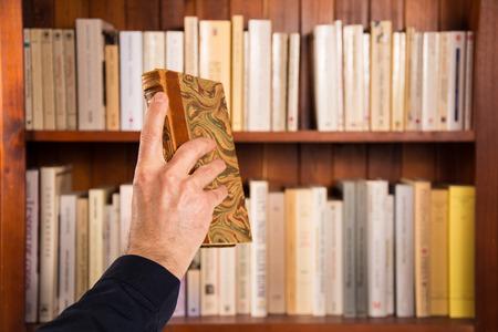 Mano masculina sosteniendo un libro frente a estanterías Foto de archivo - 85312355