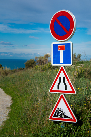 Vertical view of French road signs on a countryside dirt road